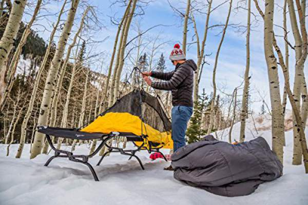 TETON Sports Outfitter XXL Camping Cot used together with a tent in snow conditions.