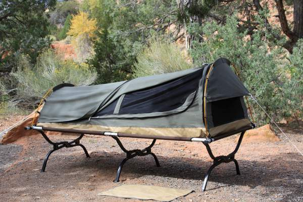This shows an extra large camping cot used as a platform for the Kodiak Canvas Swag 1 Person tent.